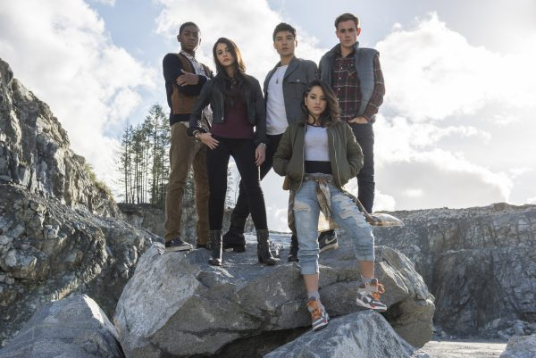 The Power Rangers cast posing on a mountain.