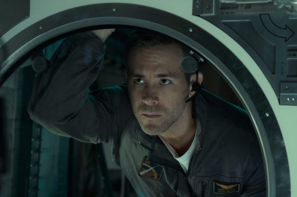 Ryan Reynolds in an astronaut jumpsuit and headset