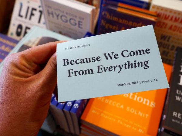 "A hand holds up a piece of paper reading, ""Because We Come From Everything"""