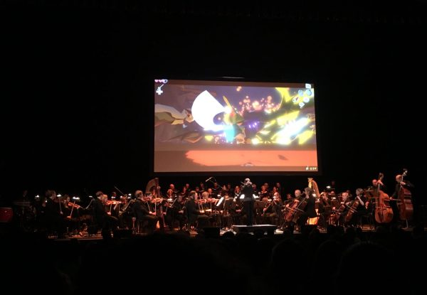 An orchestra plays below a large cloth screen displaying gameplay footage from a Zelda game