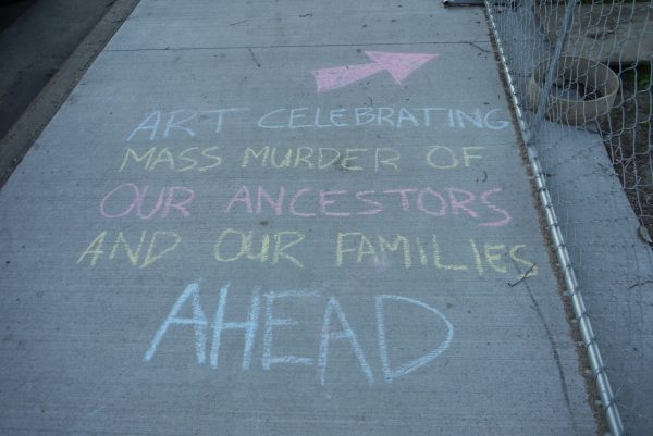 "A chalk message on the sidewalk by the Sculpture Garden reading, ""Art celebrating mass murder of our ancestors and our families ahead"""