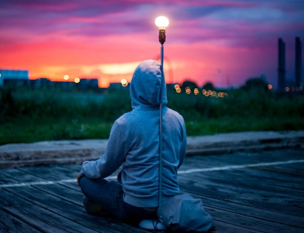 A person in a hoodie watches the sunrise