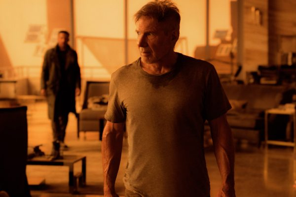 A ragged Rick Deckard, played by Harrison Ford, stands mid-frame in a sweat-soaked t-shirt, while Officer K, played by Ryan Gosling, stands out of focus to the left.