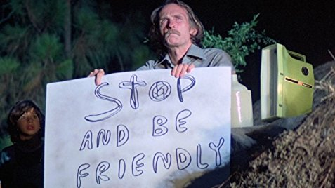 "A man holds a sign that reads ""Stop and Be Friendly."""