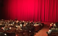 The closed stage curtains and waiting audience