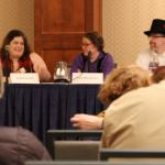 Rachel Swirsky and Lyda Morehouse talk as three other panelists and the audience listen