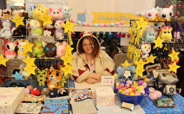 An Artist Alley vendor and her handmade stuffed creations for sale
