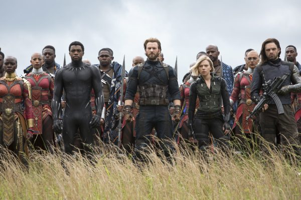A promotional photo for Avengers: Infinity War. Black Panther, Captain America, Black Widow, and Bucky Barnes stand shoulder-to-shoulder, with dozens of Wakandan soldiers behind them.