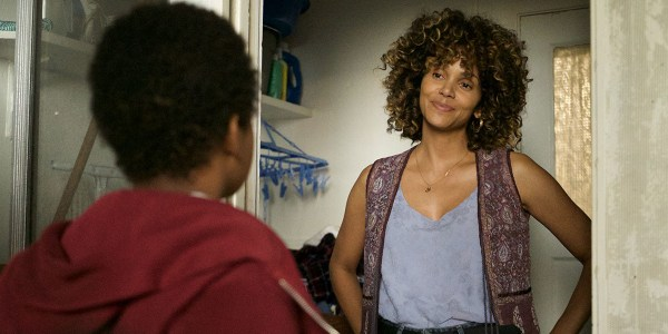 Halle Berry's character stands in front of a young boy with a smirk on her face.