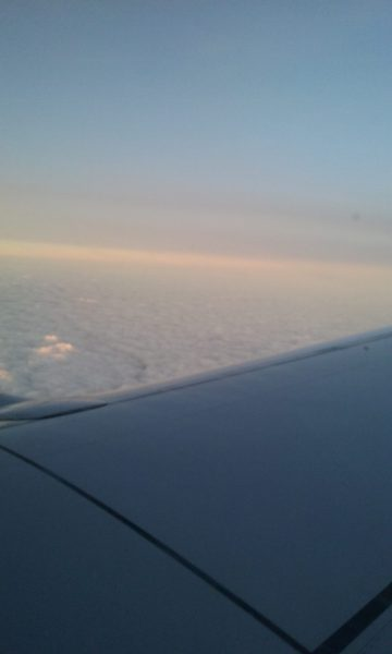 The wing of a plane overlooking clouds