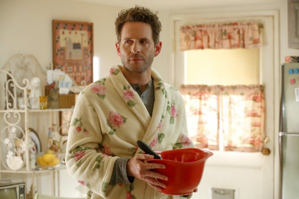 Glenn Howerton's character, Jack, wearing a bathrobe and holding a mixing bowl in a kitchen.