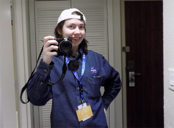 The author in a backwards white baseball cap which flattens their long, straight dark brown hair, a yellow nametag with a blue NASA lanyard, holding a black DSLR camera up, and wearing the greatest jean shirt with a NASA insignia on it the world has ever seen