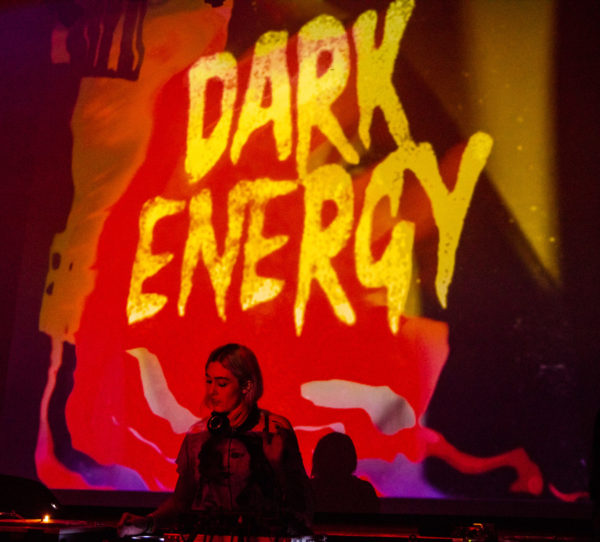 DJ in front of Dark Energy banner