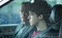 Alex Lawther seen through a wet car window