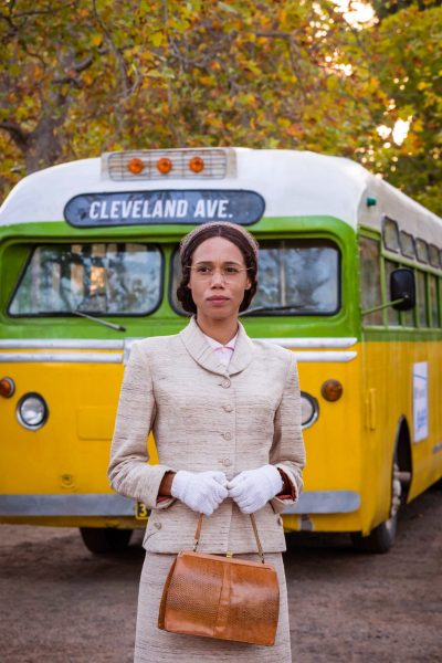 Rosa Parks stands in front of a bus