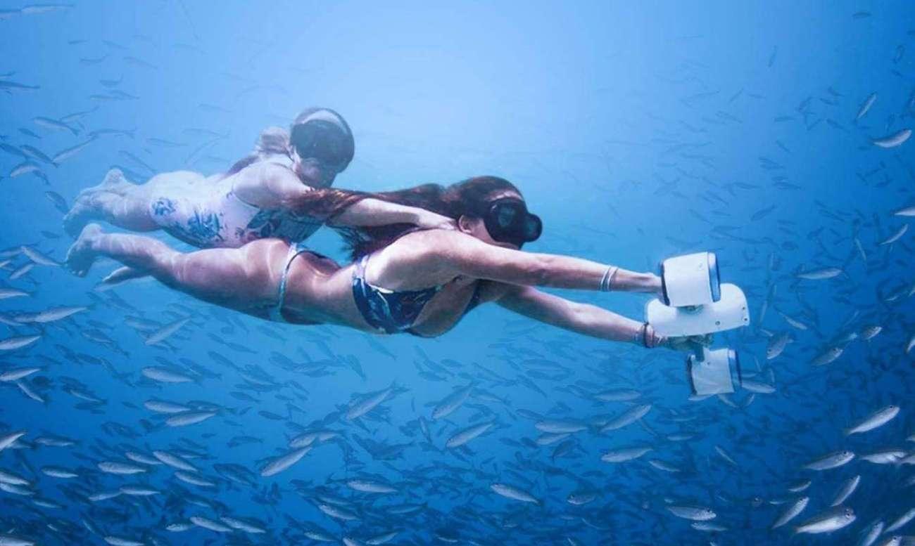 Dos chicas en el mar con gafas snorkel propulsadas por un sea scooter más vendido de amazon de la marca WhiteShark