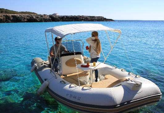 Barco de alquiler con mesa para comer en la zodiac medline 550 neo fondeada cerca de calan Bosch y cala Galdana