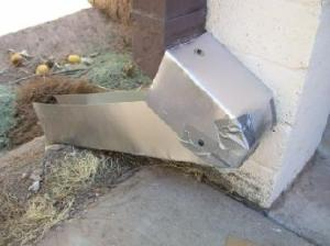 Gutter downspout with fabricated redirected channel made of aluminum flashing.