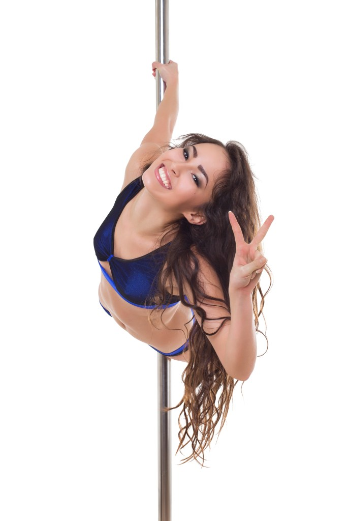 Young brunette making a peace sign with her fingers and smiling while hanging on to the pole