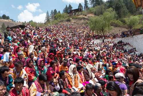 The crowds fill the hillside in their colorful dress.