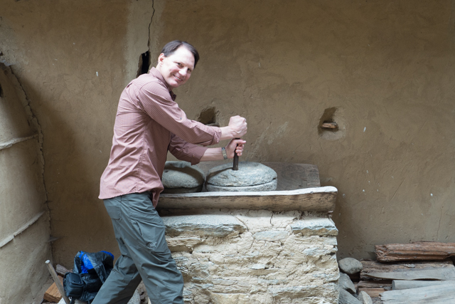 Mark having a go at grinding rice.