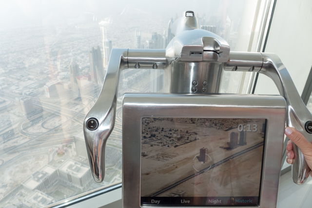 View from the observation deck of the Burj Khalifa - looking at a foreground picture of Dubai from the 1970s, with a view of today's Dubai in the background.