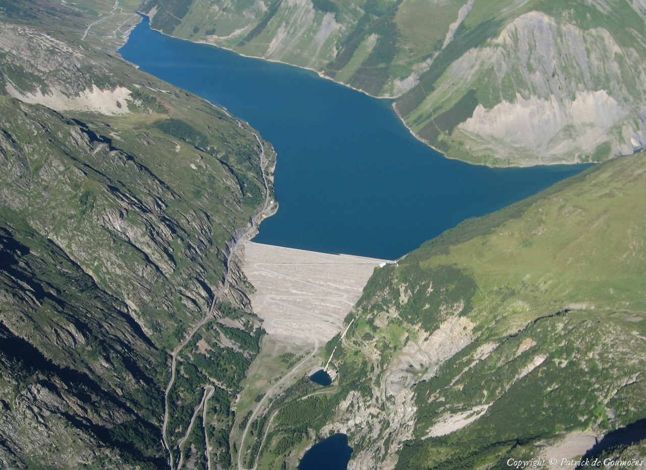 "Aerial view of the Barrage de Grand Maison (roughly translated as ""Big Dam House"").  The road along the left leads to the Col du Glandon, a 6,300 foot pass in the French Alps."