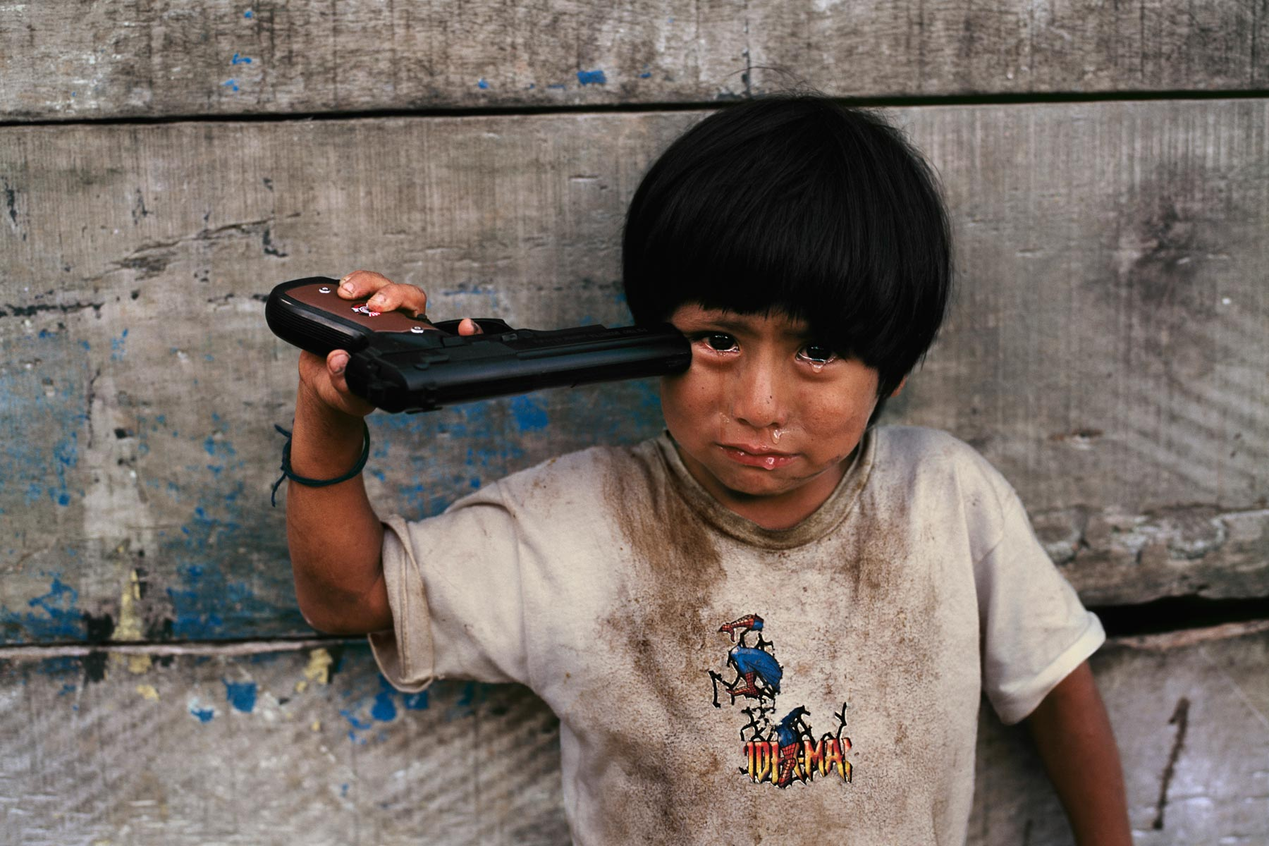 Steve McCurry photo from Peru. The caption says it is a toy gun.