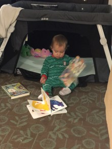 Reading to herself with the crib door open