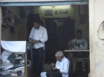 Várias lojas de alfaiataria e costura com máquinas antigas movidas a ser humano