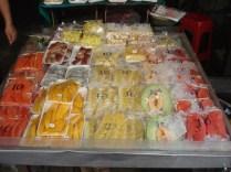 As frutas, muito coloridas, são vendidas assim e as pessoas vão comendo pelas ruas usando espetos que são dados junto