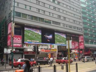 Dois telões enormes fazendo propaganda na fachada do prédio