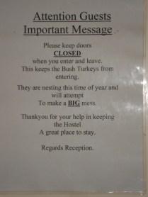 Aviso na porta do banheiro para evitar os Bush Turkeys