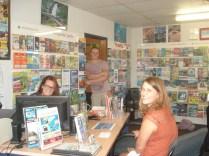 Recepção e equipe do hostel: Ahsley (inglês) em pé, Samanta (inglesa) atrás do monitor e Franciska (alemã).