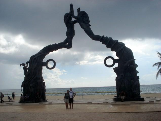 Portal Maya que foi construído em 2012. Homem e mulher, de mãos dadas, esculpidos em bronze, sendo empurrados para cima numa espiral de vento e água