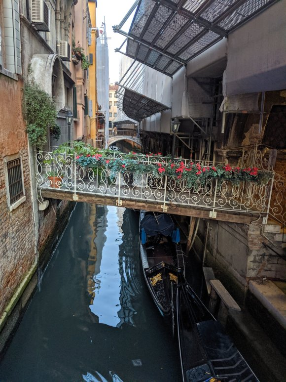 A small canal with gondola, with bridge connecting two buildings