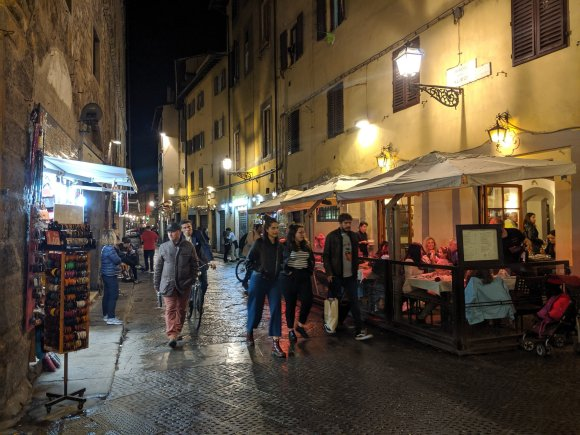 Night street scene with people walking outside shop and restaurant, Florence, Italy