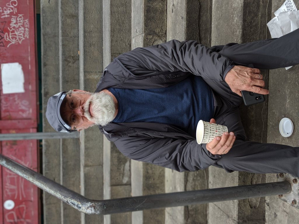 Adriel sitting on steps of Mercato Centrale in Florence, Italy holding cold brew coffee cup