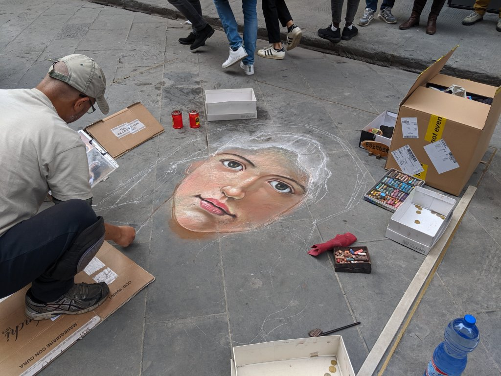 Sidewalk artist drawing portrait of woman in Florence, Italy on All Saints Day