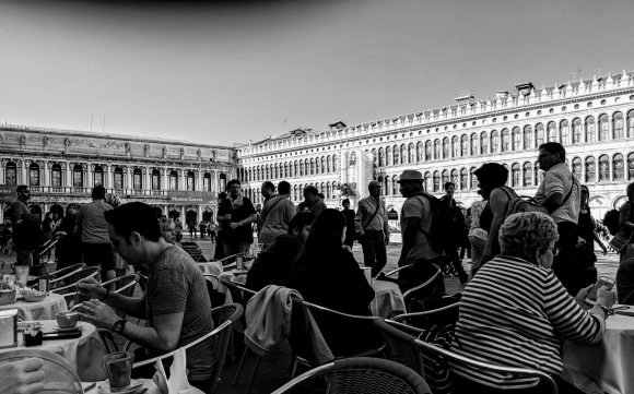 Black and white photo of people sitting at a cafe on Saint Mark's Square, Venice, Italy