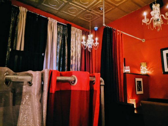 A darkened room with drapes and deep red walls