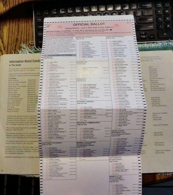 A picture of the entire, 2018 California Primary Election ballot laying over the state voter guide in the background on a table with a computer keyboard