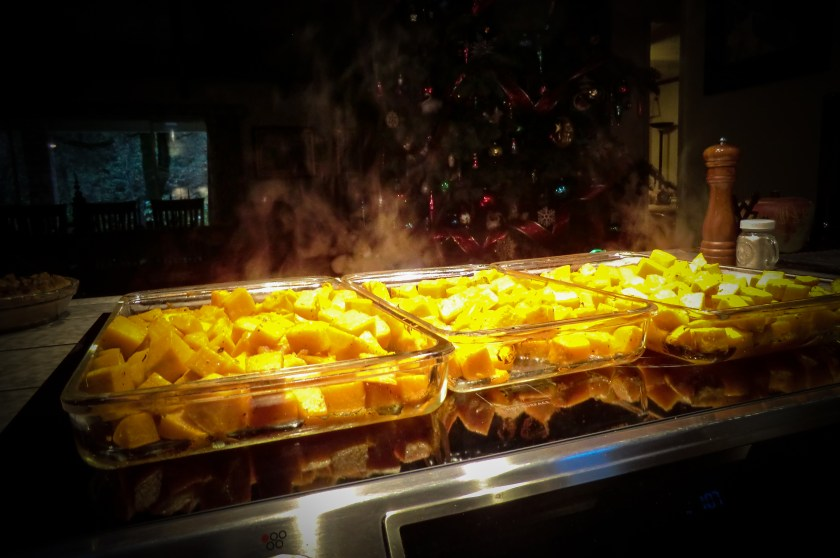 three steaming hot casserole dishes full of cubed, butternut squash just out of the oven, resting on top of the oven