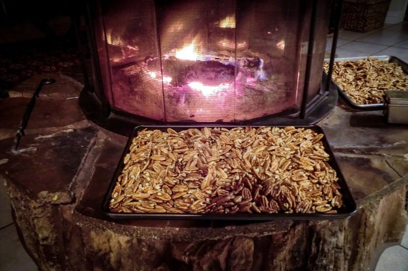 cookie sheets of pecans curing by the fire