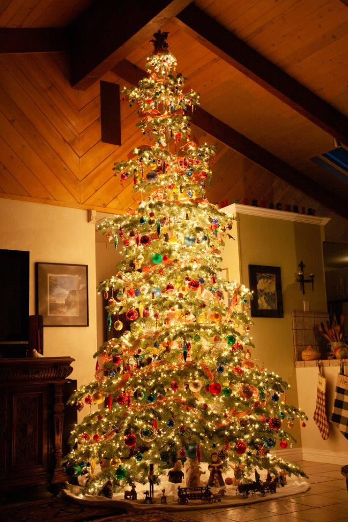 Picture of a lit, decorated Christmas tree in a house a night. Thousands of lights and hundreds of colorful and unusual ornaments. Stunning, in a room with a high, wooden ceiling