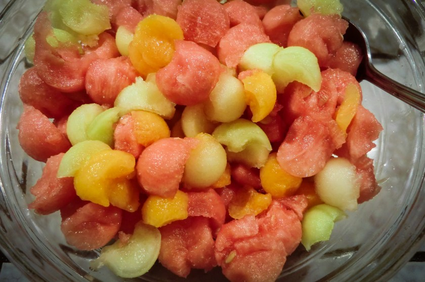 a bowl with three different colors of melon balls, yellow, green and red