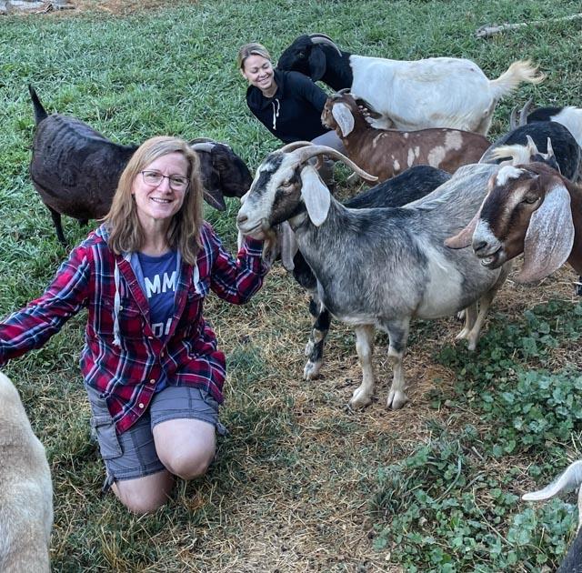 two women petting goats