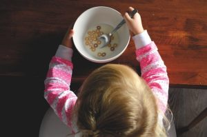 young girl holding a bowl with cereal and milk