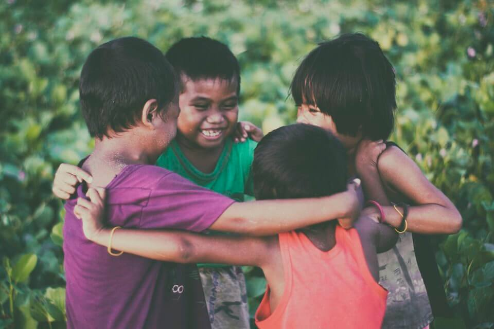 a group of children hugging in a circle