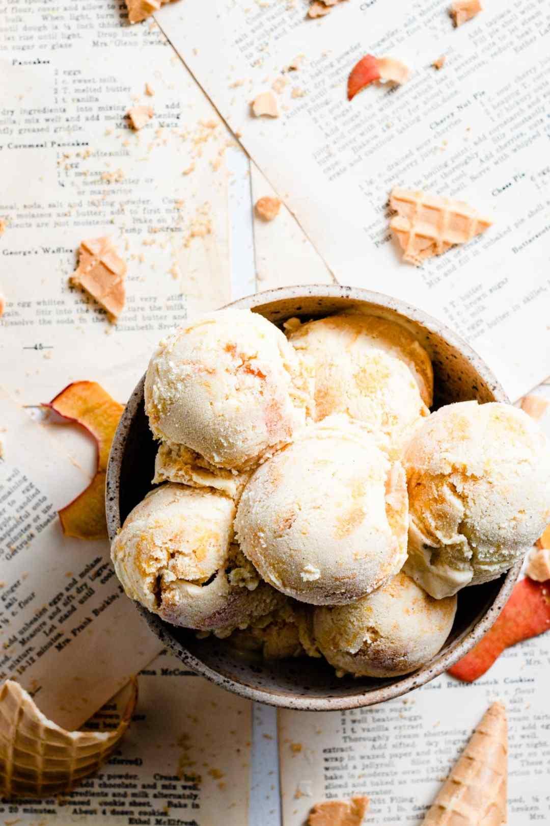 Peach ice cream scoops in a bowl.